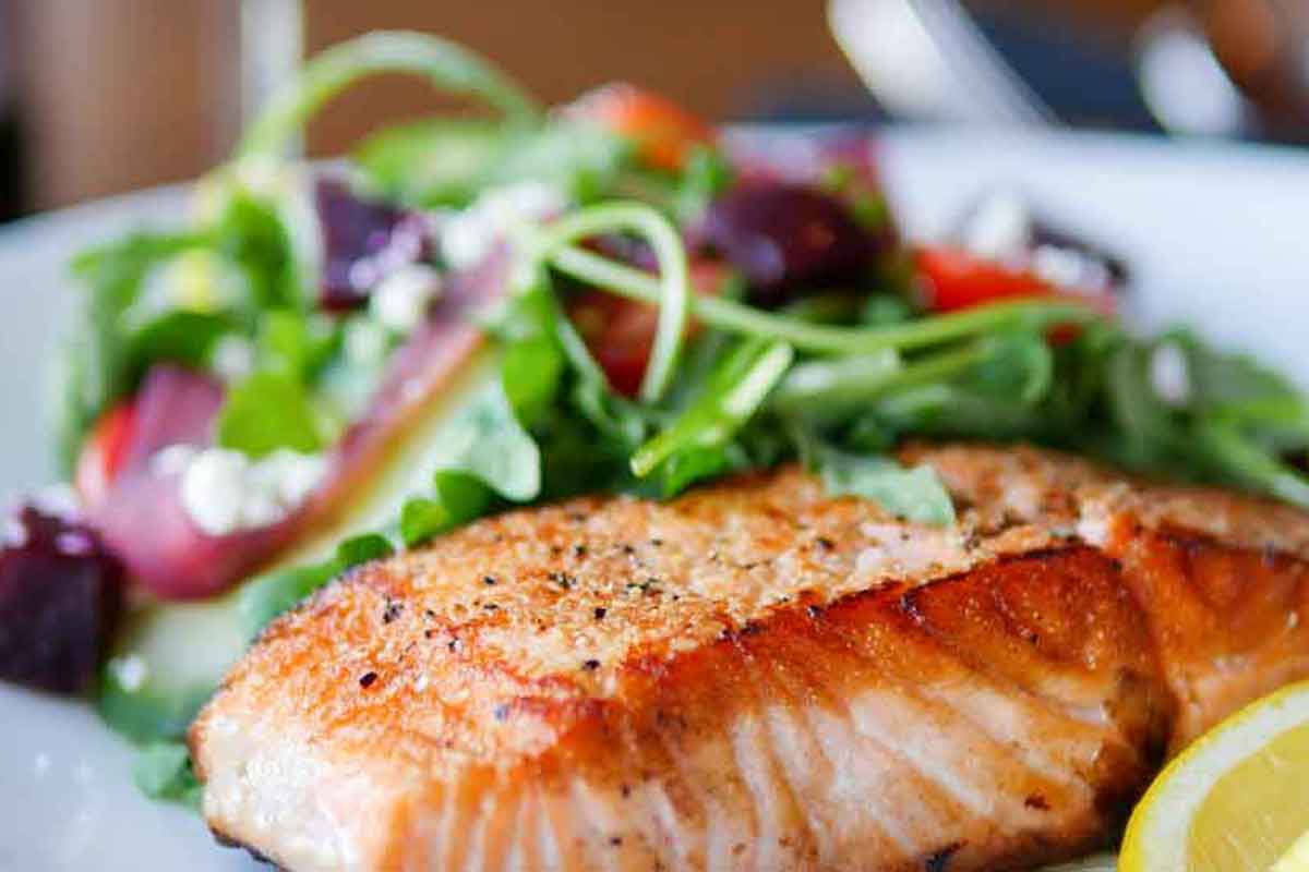 A piece of seasoned salmon cooked perfectly with a delicious fresh salad and a slice of lemon