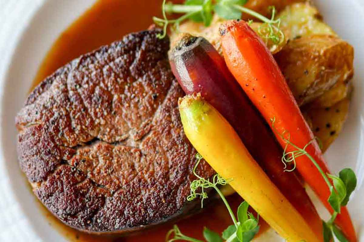 A large portion of steak with tri-color carrots and potatoes and a herb garnish with beef au jous