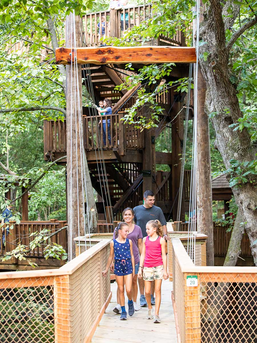 Family entering Treetop Village on wooden bridge at Arbor Day Farm