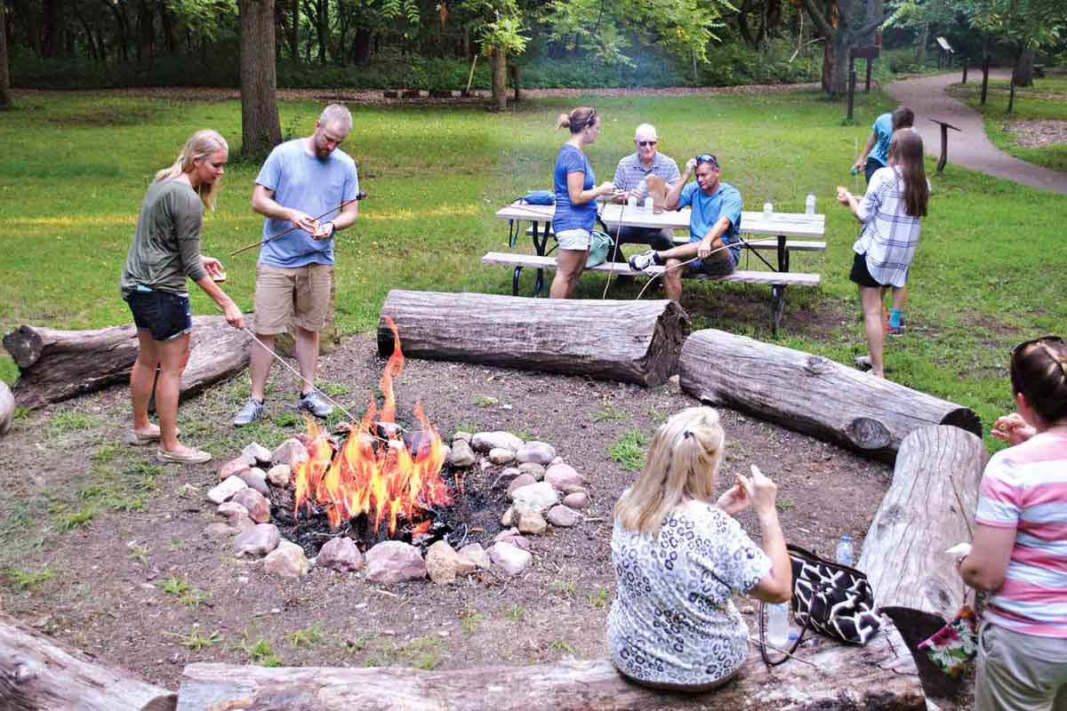 people roasting s'more during the daytime around a campfire with wooden log benches