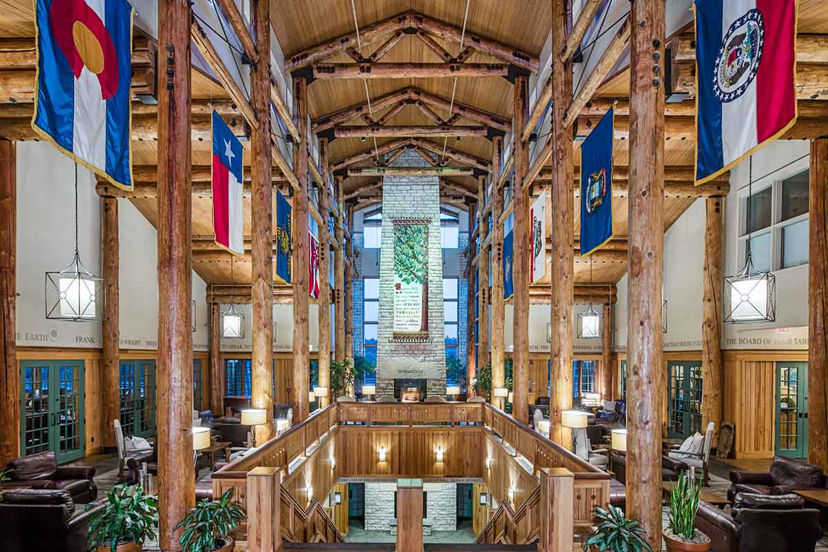 Main entryway view with flags, wooden lodge beams, and bright views