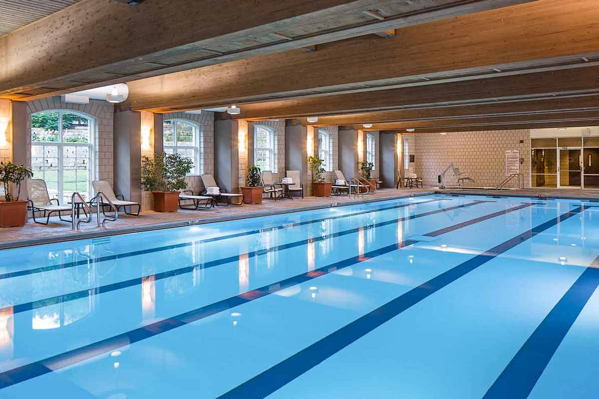 A very large indoor pool with reclining chairs and accessible entrances to the pool