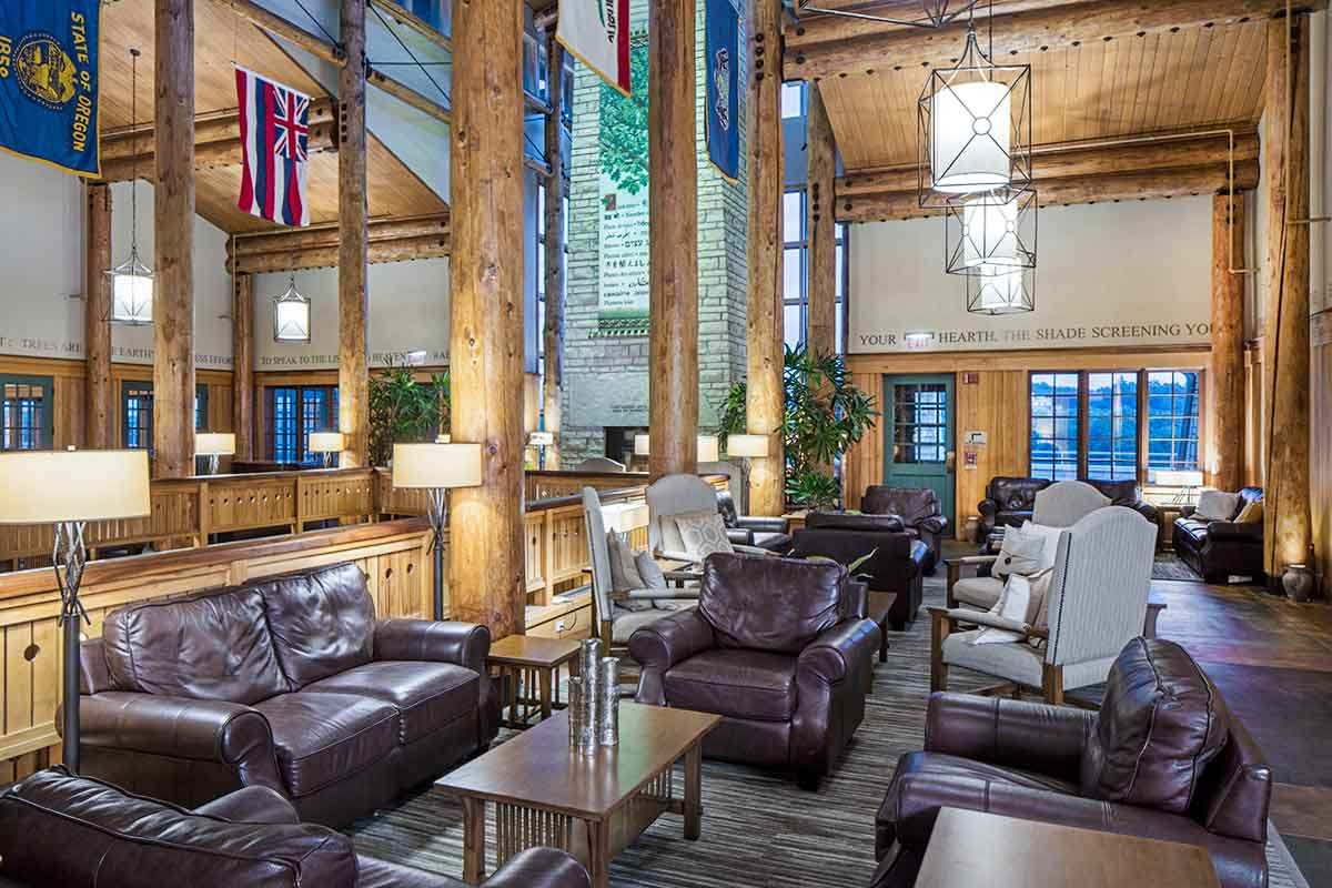 Lodge with tall wooden beams, comfy leather chairs, tables, and sunny lighting