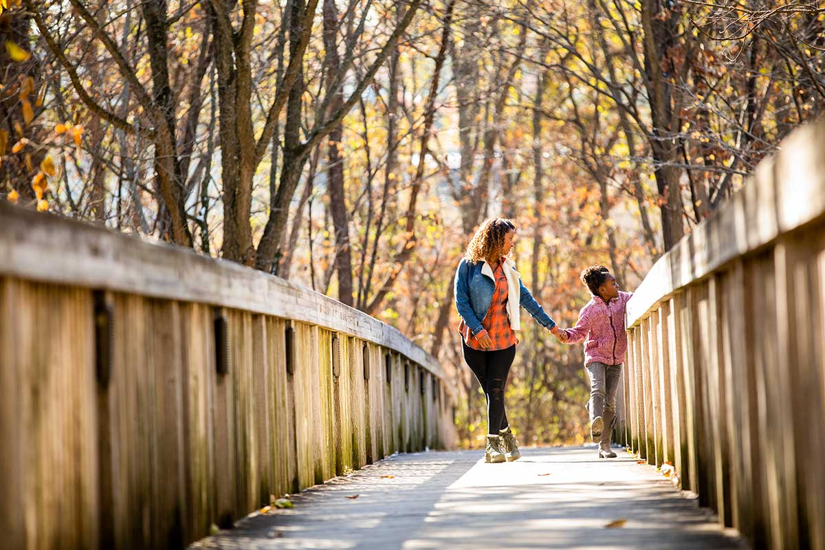 Mom and daughter walking on trail bridge in autumn