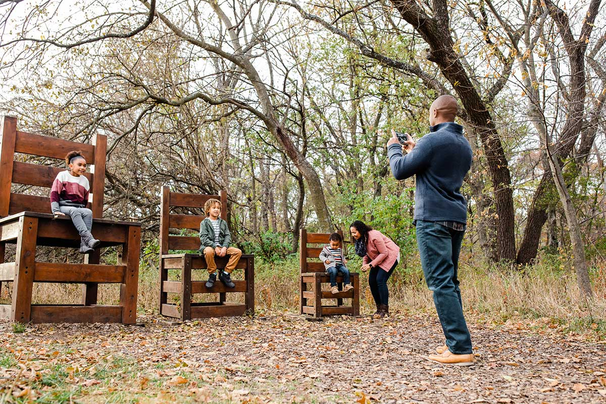 Family posing with large decorative wooden chairs on trail