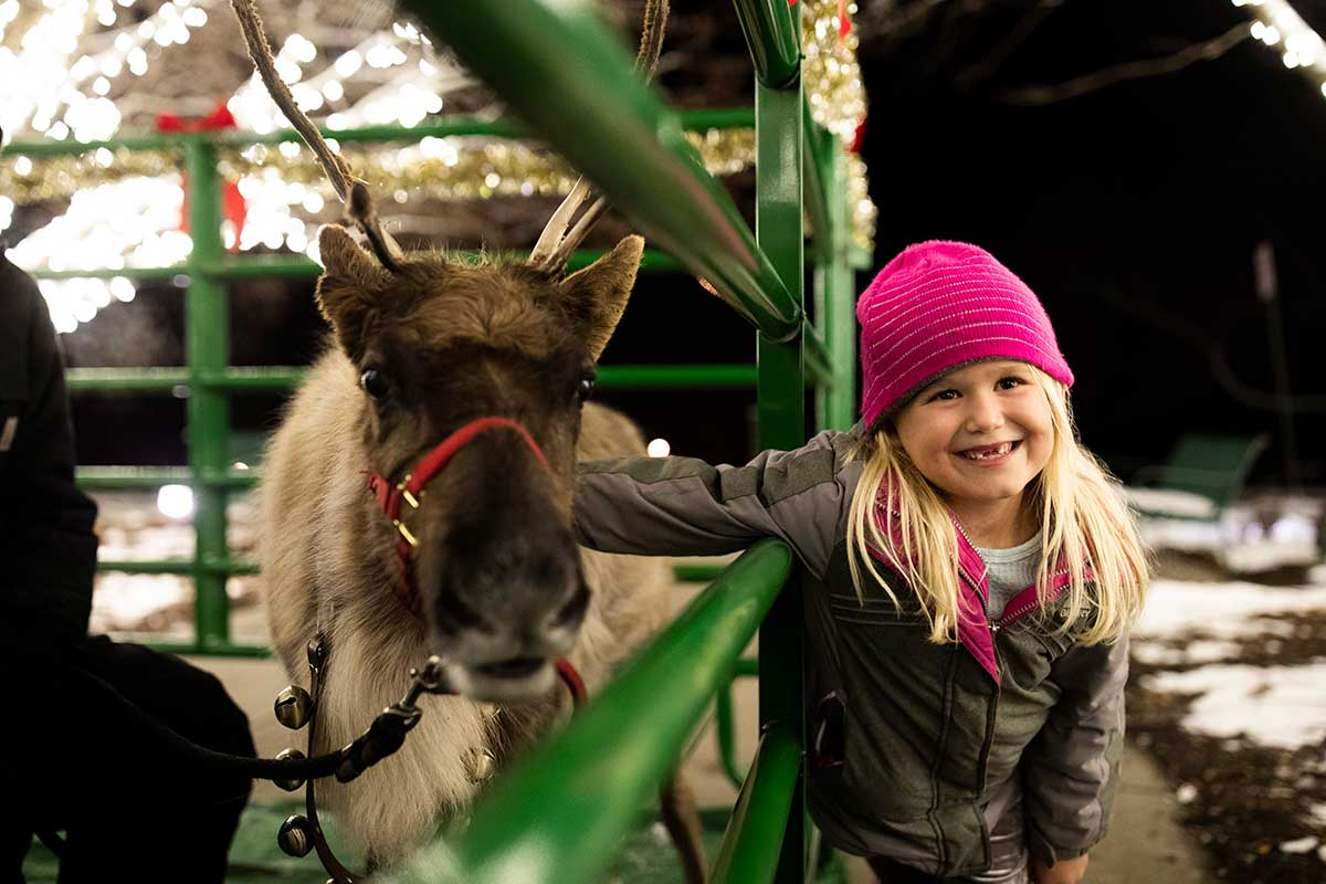 Little girl with reindeer, Christmas time at Arbor Day Farm