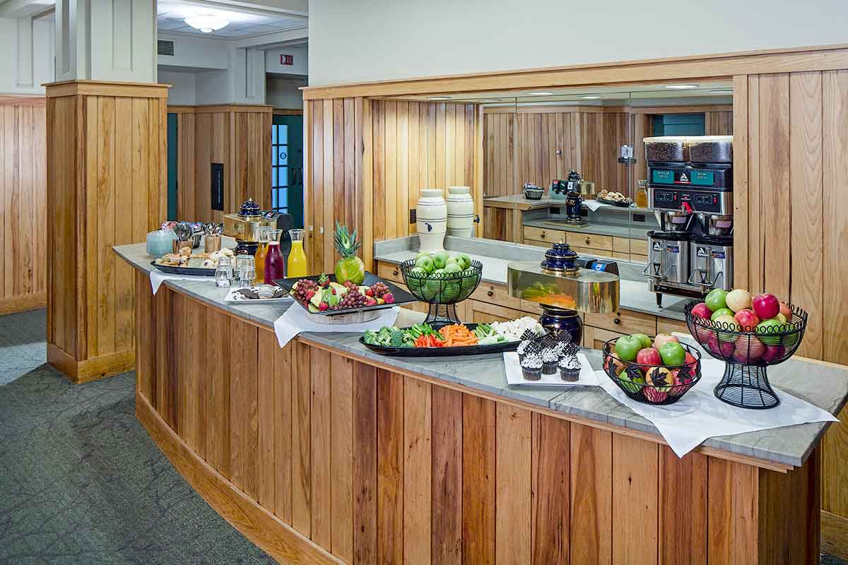 A picture of a fruit buffet with apples, cupcakes, coffee maker, juices, and assorted pastries
