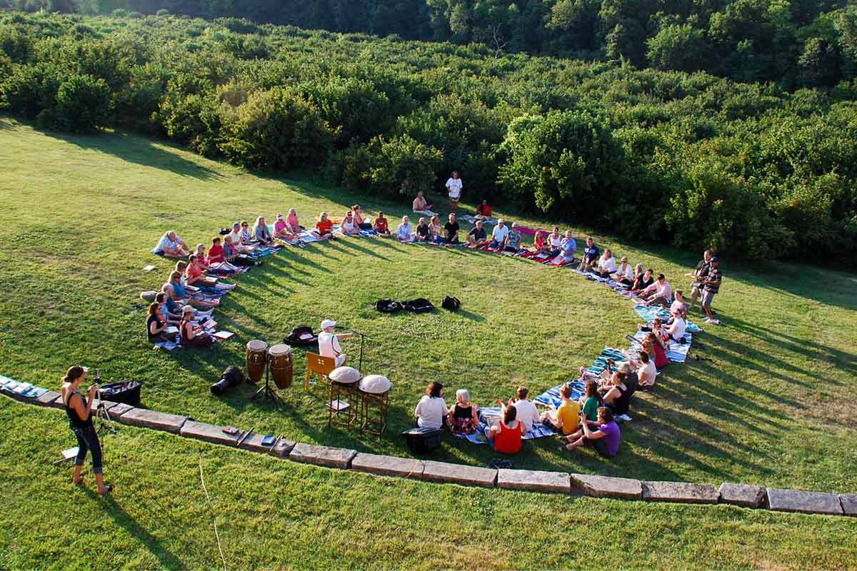 An outdoor setting featuring people sitting in a circle with bongo drums