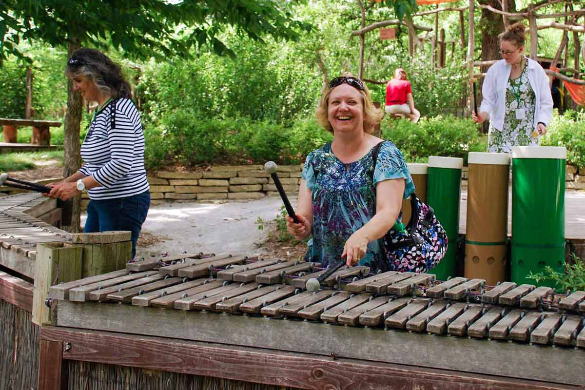 People playing on three large outdoor xylophones